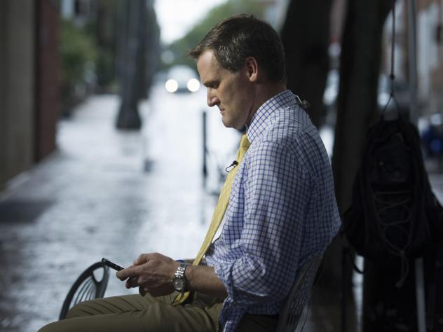 Mike Signer, mayor of Charlottesville at the time, checks his phone while waiting to speak days after Heather Heyer was killed during the Unite the Right rally in 2017. These days Signer travels the country presenting his city's experience as a cautionar