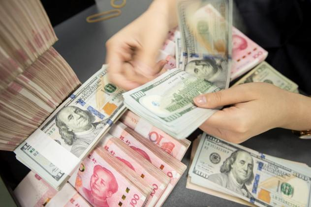 A Chinese bank employee counts 100-yuan notes and dollar bills at a counter in Nantong, in China's eastern Jiangsu province, on Tuesday.