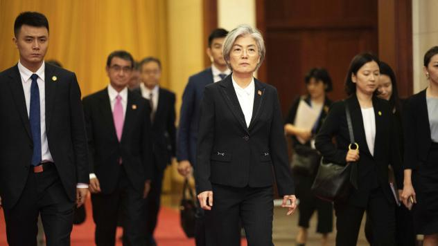 South Korea has announced it will withdraw from a 2016 military intelligence-sharing pact with Japan. Here, South Korean Foreign Minister Kang Kyung-wha, center, and Japanese Foreign Minister Taro Kono, trailing at left, walk in Beijing's Great Hall of t
