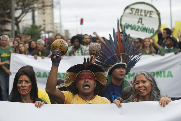 Indigenous people protest in defense of the Amazon in Rio de Janeiro on Sunday. Experts from the country's satellite monitoring agency say most of the fires are set by farmers or ranchers clearing existing farmland, but the same monitoring agency has rep