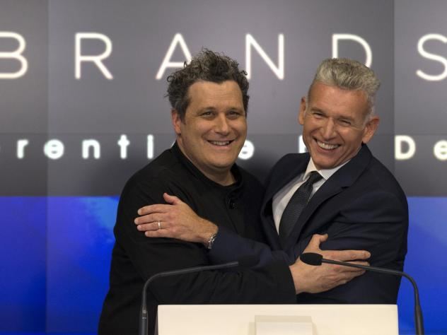 Designer Isaac Mizrahi (left) embraces Robert D'Loren, CEO of Xcel Brands, which once manufactured 70% of its clothes in China. Today that's down to about 20%. The company now manufacturers in a variety of countries, including Indonesia, India and Sri La