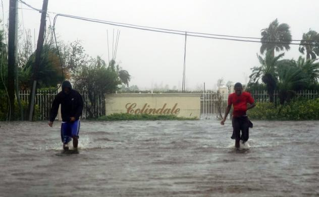 Residents wade through a street flooded with water brought on by Hurricane Dorian in Freeport, Bahamas, on Tuesday. The storm spent most of Monday and into the morning Tuesday essentially stalled out over the Bahamas, relentlessly pounding the islands wi