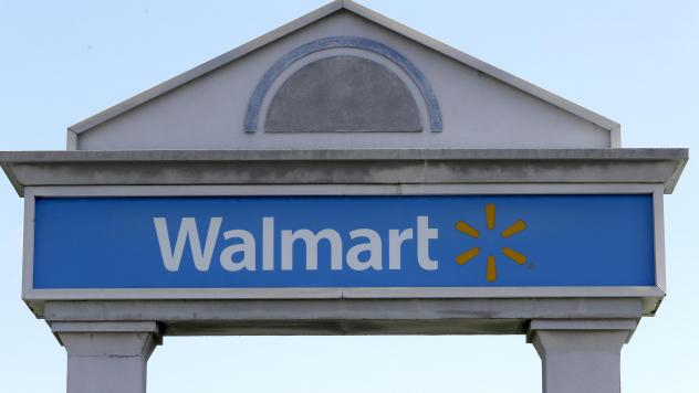 A Walmart logo forms part of a sign outside a Walmart store, Tuesday, Sept. 3, 2019, in Walpole, Mass. Walmart is going back to its folksy hunting heritage and getting rid of anything that's not related to a hunting rifle after a mass shooting this summe