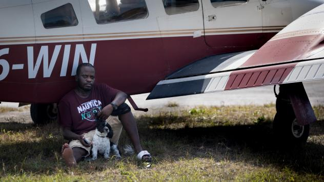 Evacuee Samazio Rolle and his dog, Logan, sit in the shade next to an airplane in the afternoon heat at a landing strip on Abaco, in hopes of catching a flight to Nassau. The pair survived Hurricane Dorian's punishing strike on the Bahamas — and now th