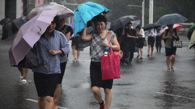 Pedestrians shield themselves from wind and rain brought by Typhoon Lingling Saturday, in Pyongyang, North Korea.
