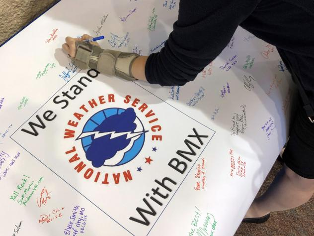 Christina Crowe signs a poster in support of the National Weather Service office in Birmingham, Ala., during a convention of the National Weather Association in Huntsville, Ala., Monday.