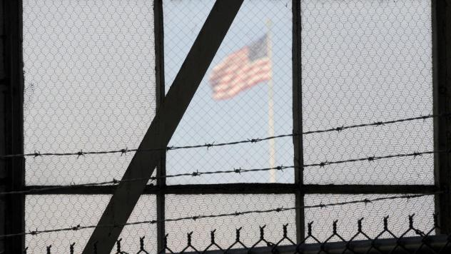 An NPR investigation finds that the military court and prison at Guantánamo Bay, Cuba, have cost taxpayers billions of dollars, with billions more expected. (Above) An American flag is seen through the war crimes courtroom at the U.S. naval base at Guan