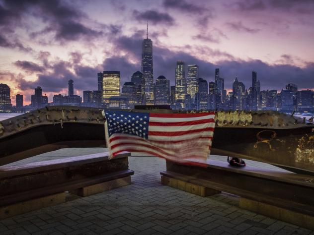 A U.S. Flag hanging from a steal girder, damaged in the Sept. 11, 2001 attacks on the World Trade Center, blows in the breeze at a memorial in Jersey City, N.J., Sept. 11, 2019 as the sun rises behind the One World Trade Center building and the re-develo