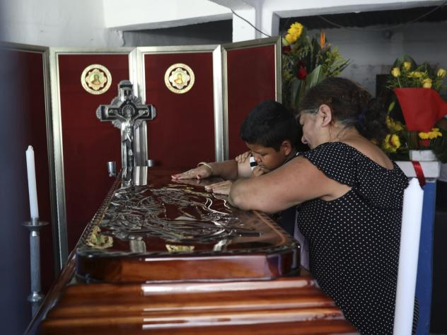 Twelve-year-old Jesús Ruiz grieves as he stands before the coffin containing the remains of his father, Mexican journalist Jorge Celestino Ruiz Vazquez, in Actopan, Veracruz, on Aug. 3. The Committee to Protect Journalists said Ruiz Vazquez was the thir