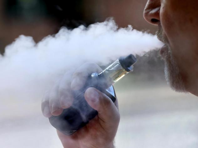 A man exhales while smoking an e-cigarette. New York Gov. Andrew Cuomo said the state will issue an emergency regulation banning certain flavored products amid a health scare linked to vaping.