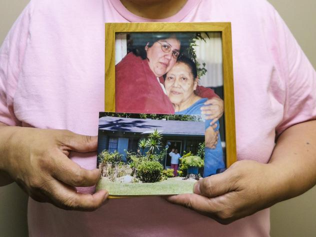 Maria Rivas holds photographs of her mother, Julia Medina, who died in 2012. Maria cared for Julia for six years at the end of her life.
