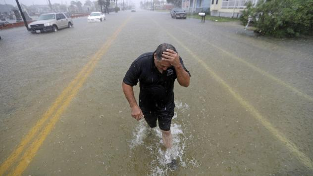 Parts of eastern Texas could see nearly 3 feet of rain through Friday, forecasters say, warning of potential flash floods from Tropical Depression Imelda. Here, Angel Marshman walks through floodwaters in Galveston after trying to start his flooded car W