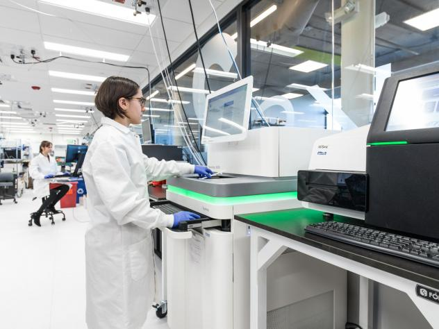 An employee of the Boston biotech company Ginkgo Bioworks runs a gene sequencing machine through its paces. The company synthesizes thousands of genes a month, which are then inserted into cells that become mini factories of useful products.