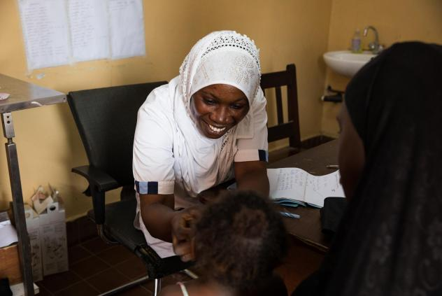 Nabia Drammeh, 27, a nurse, talks with Maram Ceesay, and her granddaughter, Awa at the Brufut Minor Health Center outside of Banjul, the Gambia. Awa's mother passed away during childbirth leaving her Maram to look after her. The 2-year-old is being treat