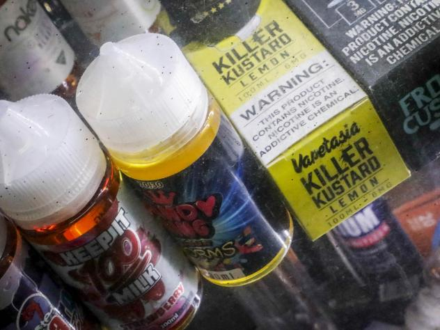 Flavored vaping solutions stand displayed at a shop in New York City. Amid a mysterious health scare apparently caused by e-cigarettes, New York and Michigan have banned the sale of flavored vaping products, while Massachusetts has banned all of them for