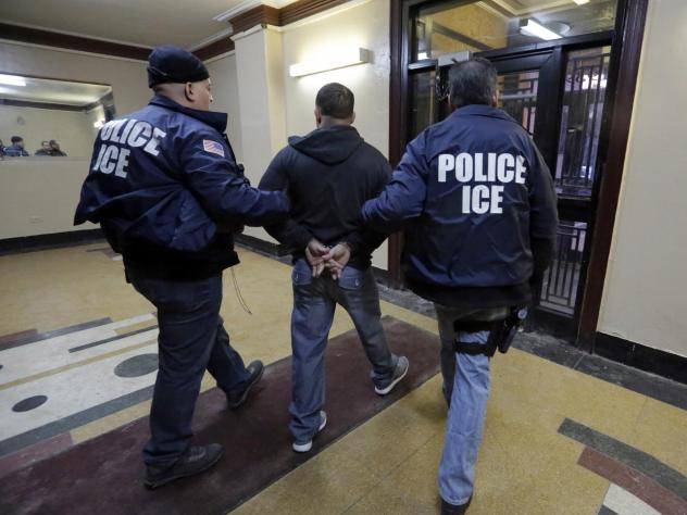 In this March 3, 2015, photo, Immigration and Customs Enforcement officers escort an arrestee in an apartment building in the Bronx borough of New York during a series of early morning raids.