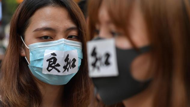 """A woman wearing a face mask with the characters meaning """"conscience"""" takes part in a protest against a government ban on protesters wearing face masks in Hong Kong on Friday."""