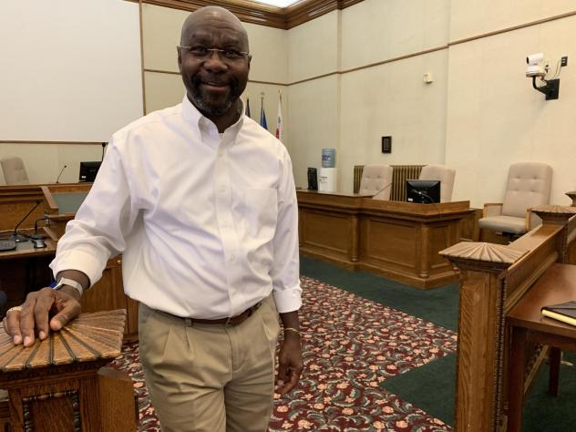 Wilmot Collins stands in the Helena City Commission chambers before a meeting. He moved to Montana in the early 1990s.
