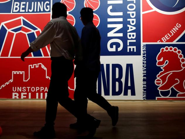 Men walk past a poster at an NBA exhibition in Beijing on Oct. 8.