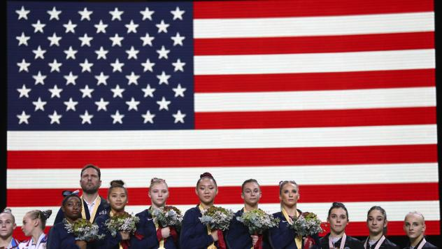 Team U.S.A. listening to the national anthem at the Gymnastics World Championships in Stuttgart, Germany. Simone Biles, third from left, wears her 21st championship medal.
