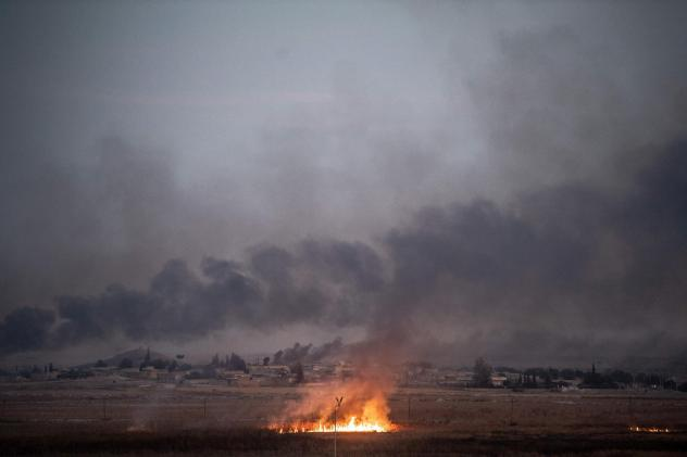 Smoke rises from the Syrian town of Tal Abyad on Thursday on the second day of Turkey's military operation against Kurdish forces. President Trump's decision to pull back U.S. forces from the area has been viewed as giving Turkey a green light for the op