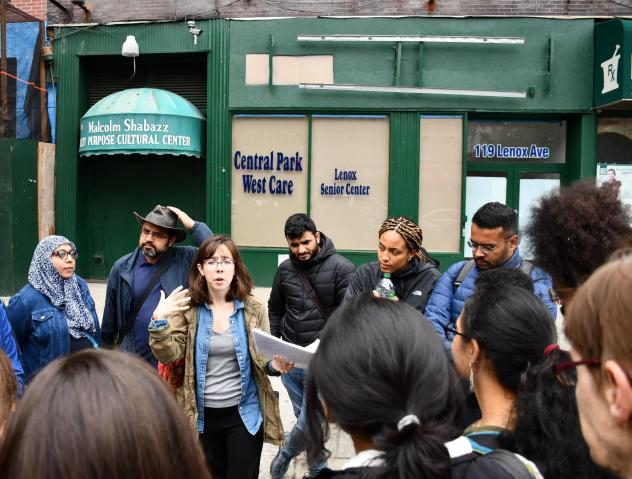 Tour participants listen to guide Katie Merriman (center) outside the Malcolm Shabaaz Mosque as she speaks about the influence of Malcolm X on the Harlem community.
