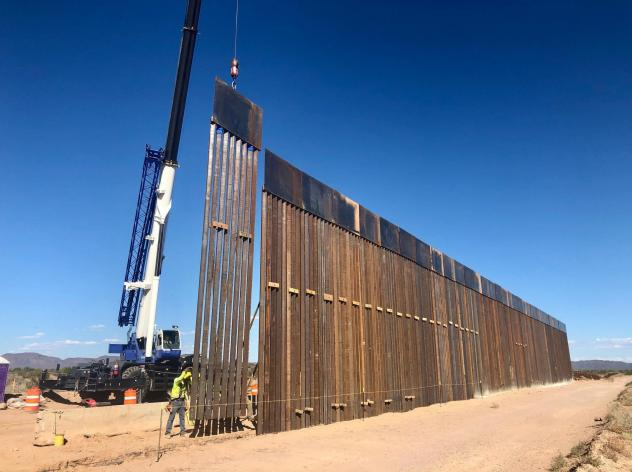 A 30-foot border barrier — as tall as a two-story building — rises from the desert near Lukeville, Ariz.