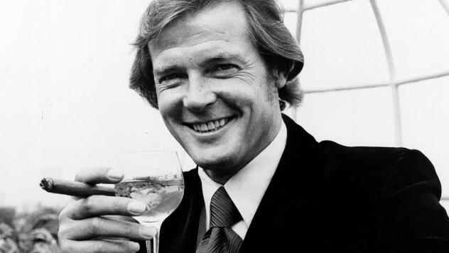 """Actor Roger Moore, who played secret agent James Bond in the '70s and '80s, holds a martini. A new book written by a former CIA agent details how restaurants and cafes """"are in many ways the lifeblood of espionage."""""""