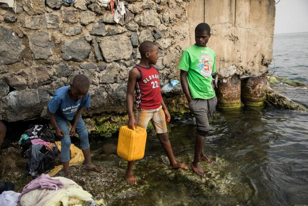 """Pascal Bitasimwa, 12, of Goma (in the red shirt) goes to Lake Kivu to fill up jerrycans with water. """"This takes me much of my time,"""" he says. """"Instead of going to study, I come first to take water."""""""