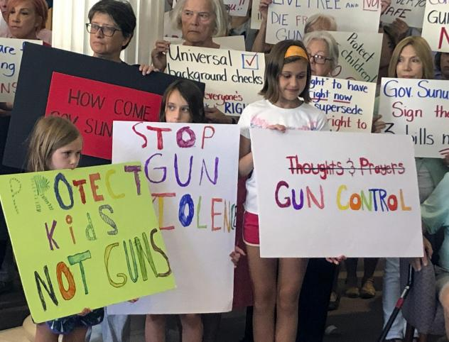 Supporters of gun control measures gather at the Legislative Office Building in Concord, N.H., in August, to urge Republican Gov. Chris Sununu to act after mass shootings in Texas and Ohio.