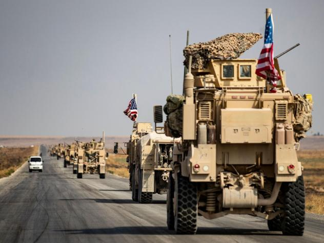 U.S. military vehicles drive on a road in the town of Tal Tamr on Sunday after pulling out of a base in northern Syria. Defense Secretary Mark Esper says some troops may remain in northeast Syria to secure oil fields.