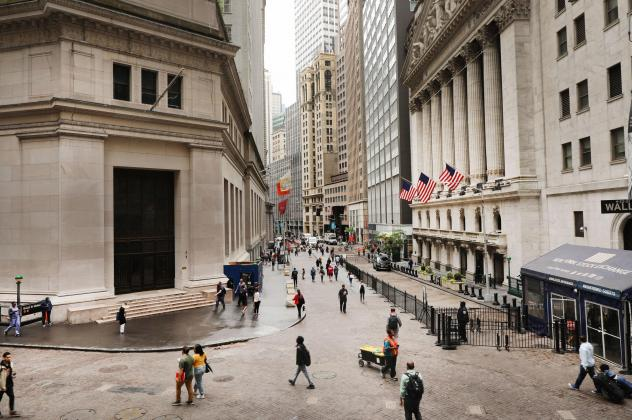 Investors are spending billions of dollars to align their portfolios with their personal values. But there's little agreement on what exactly qualifies — or disqualifies — an investment option from being marketed as sustainable. Above, pedestrians wa