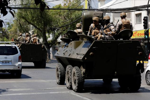 A Chilean military convoy patrols the streets of the capital of Santiago on the fourth day of unrest on Tuesday.