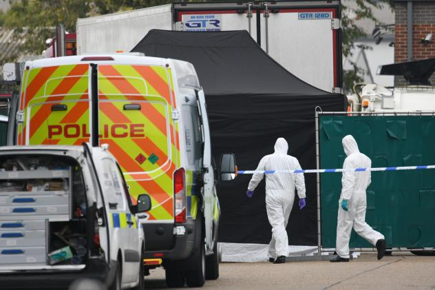 A police forensic investigation team walks near the site where 39 bodies were discovered in the back of a truck on Wednesday in Waterglade Industrial Park in Grays, England. Police believe the truck is from Bulgaria, a member of the European Union, and t