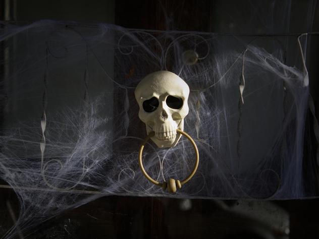 A skull door knocker and cobweb decorations on the day before Halloween in Philadelphia.