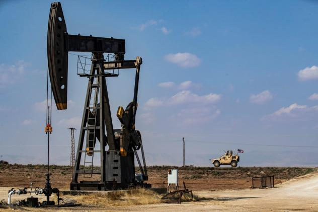 A U.S. military vehicle drives past an oil pump jack in the countryside of Syria's northeastern city of Qamishli. President Trump is leaving some U.S. troops in Syria, with the goal of controlling Syria's oil fields. But legal experts say exploiting the