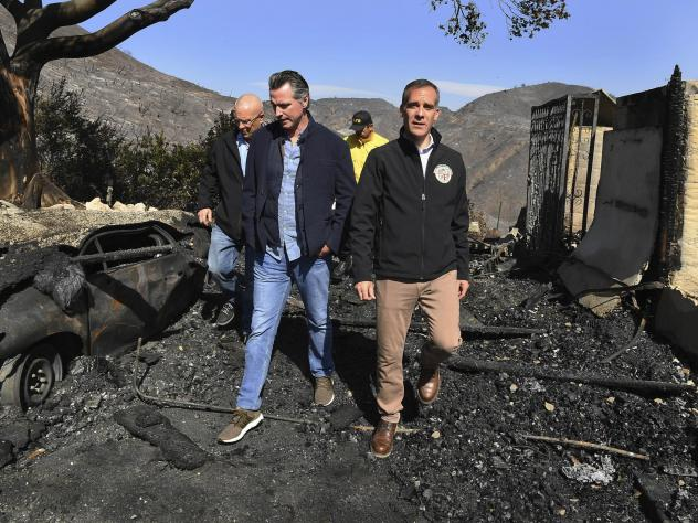 From left, LA City Councilman Mike Bonin, California Gov. Gavin Newsom and LA Mayor Eric Garcetti tour a burned home in Brentwood, Calif., on Tuesday.