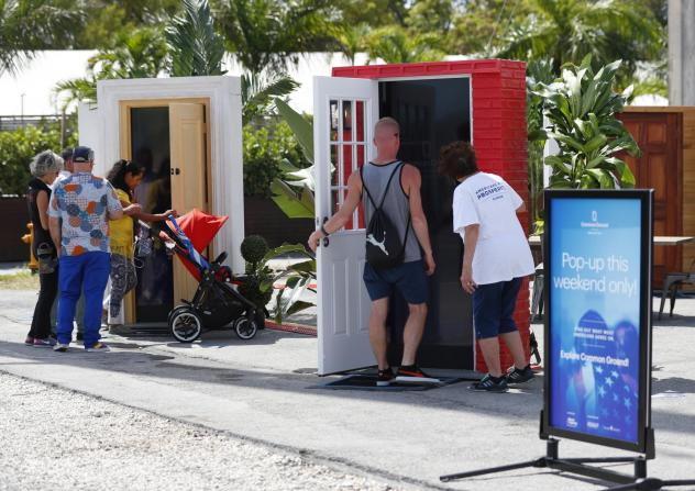 Passersby open doors to watch videos at an installation titled <em>Common Ground,</em> which shares personal stories of immigrants who are young entrepreneurs, war heroes and farmers in Miami on Oct. 3. The installation, organized by groups that get fund