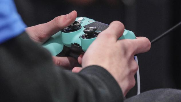 A person holding a PlayStation 4 controller. China is imposing curfews and regulations on video game playing minors.
