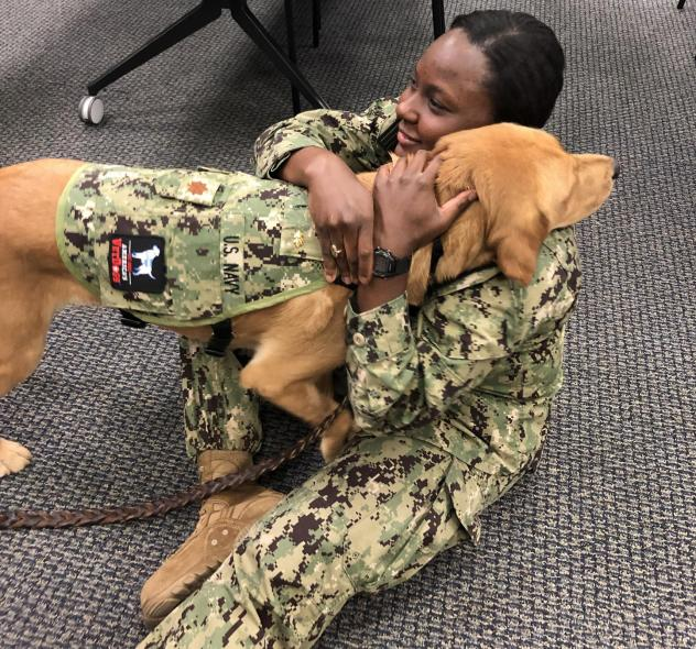 Brelahn Wyatt, a Navy ensign and second-year medical student, shares a hug with Shetland. The dog's military commission does not entitle him to salutes.