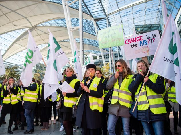 """Flight picketing in front of the Munich Airport Thursday, some holding signs with slogans that read """"Change is in the air???"""" Lufthansa has cancelled a total of 1300 flights due to the announced 48-hour strike by flight attendants."""