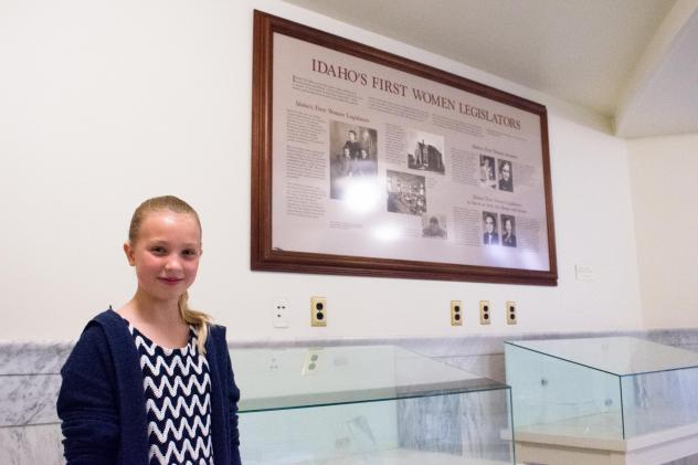Anna Wiese, 11, stands in front of a plaque in the state Capitol building commemorating Idaho's first female legislators. She originally found the plaque tucked away in a forgotten corner last year and wrote a letter to get it moved.