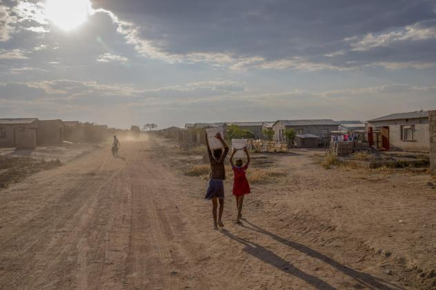Girls carry containers of water filled from the local communal tap Zimbabwe, which is in the grip of a nationwide drought that has been linked to climate change.