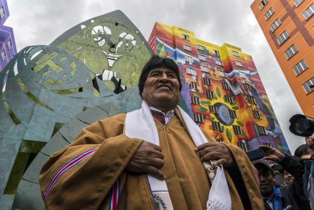 President Evo Morales at the inauguration of new buildings in a housing project in 2016. The indigenous Aymara artist Roberto Mamani Mamani painted murals over a building facade.