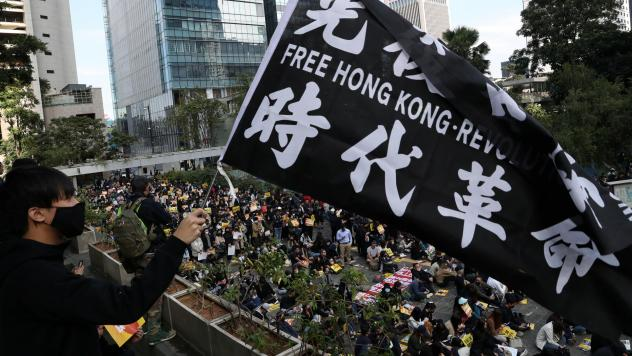"""""""China urges the U.S. to correct its mistake and stop meddling in Hong Kong affairs,"""" a government spokesperson says, as China retaliates for U.S. support of pro-democracy demonstrators. Here, an activist holds a flag at a lunchtime protest Monday at Cha"""