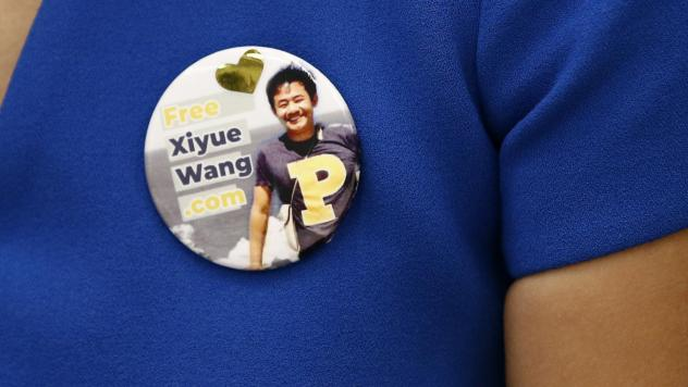 Hua Qu, the wife of Xiyue Wang, a Princeton University graduate student being held at an Iranian prison, wears a button bearing a picture of her husband as she speaks at a news conference to mark the third anniversary of his imprisonment, Aug. 8, 2019, i