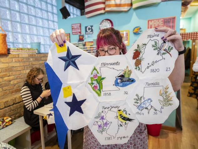 Jenni Grover holds a collection of finished patches from a quilt created by more than 100 volunteers across the country. The plans for the quilt were discovered at the estate sale of 99-year-old Rita Smith, who died earlier this year. Several dozen volun