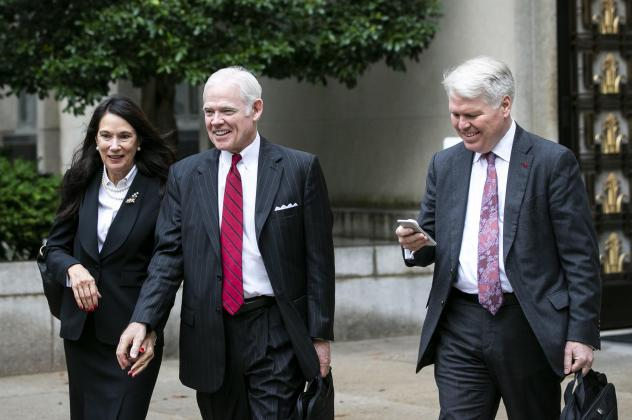 Attorney Charles Cooper, representing former national security aide Charles Kupperman (center) departs federal court in Washington in October. On Tuesday, Cooper asked a federal court to keep alive a lawsuit centered on a now-withdrawn subpoena filed by