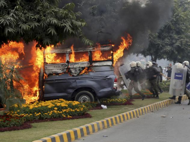 Police officers gather next to a burning police vehicle set on fire by angry lawyers during clashes in Lahore, Pakistan, on Wednesday.