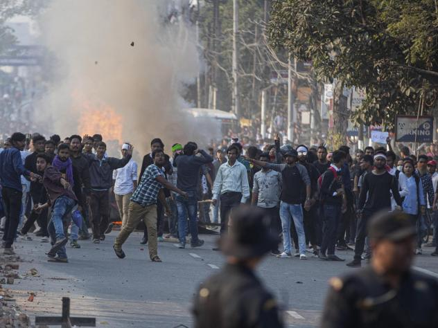 Protesters throw stones at security officers during a protest against the Citizenship Amendment Bill in Gauhati, India, on Wednesday.